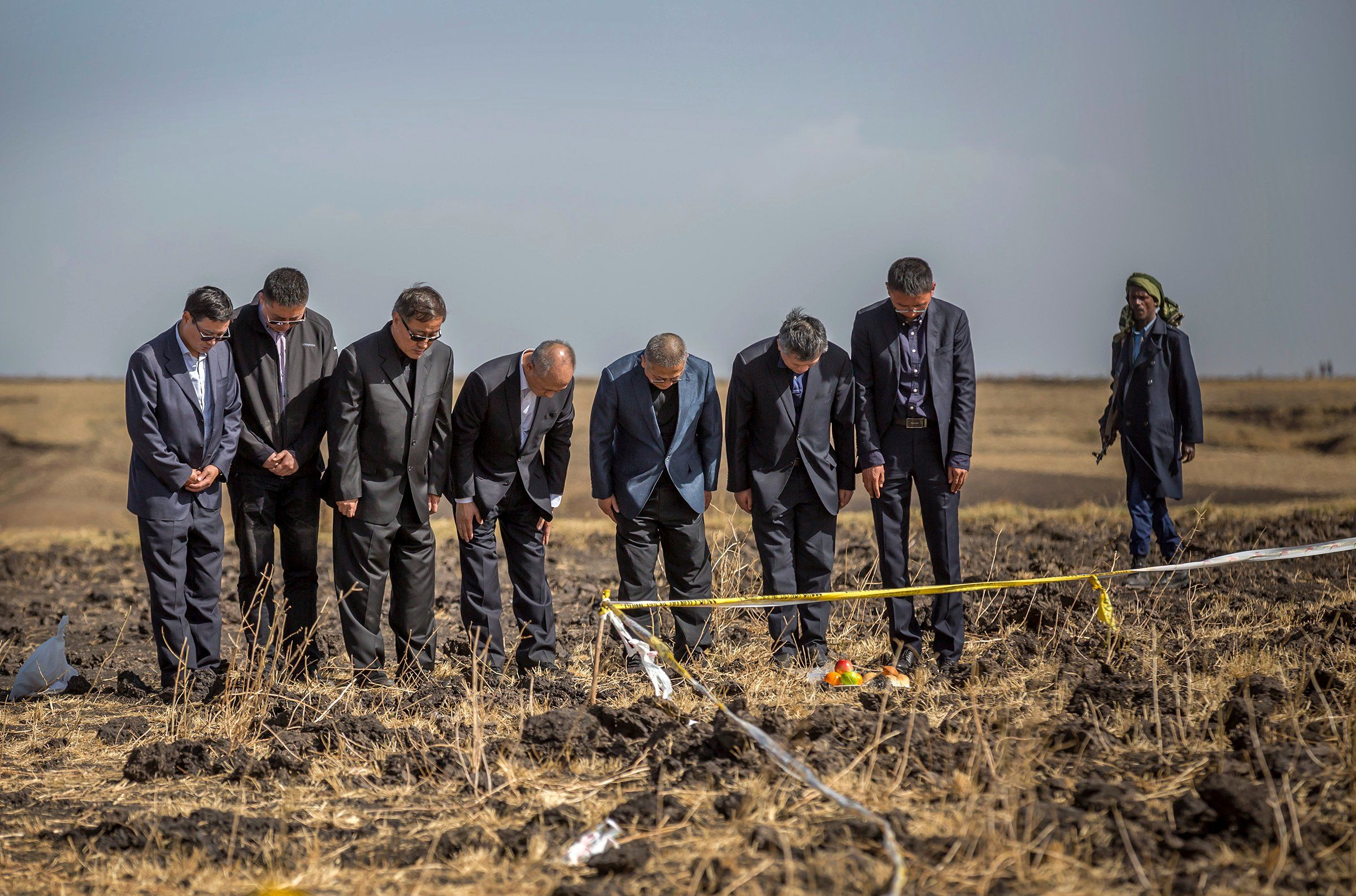 Aviation officials pray at the site of the Ethiopian Airlines crash, shortly after takeoff, near Bishoftu, southeast of Addis Ababa, on March 12. Following the crash that killed all 157 people, dozens of countries and airlines grounded Boeing's 737 Max 8.