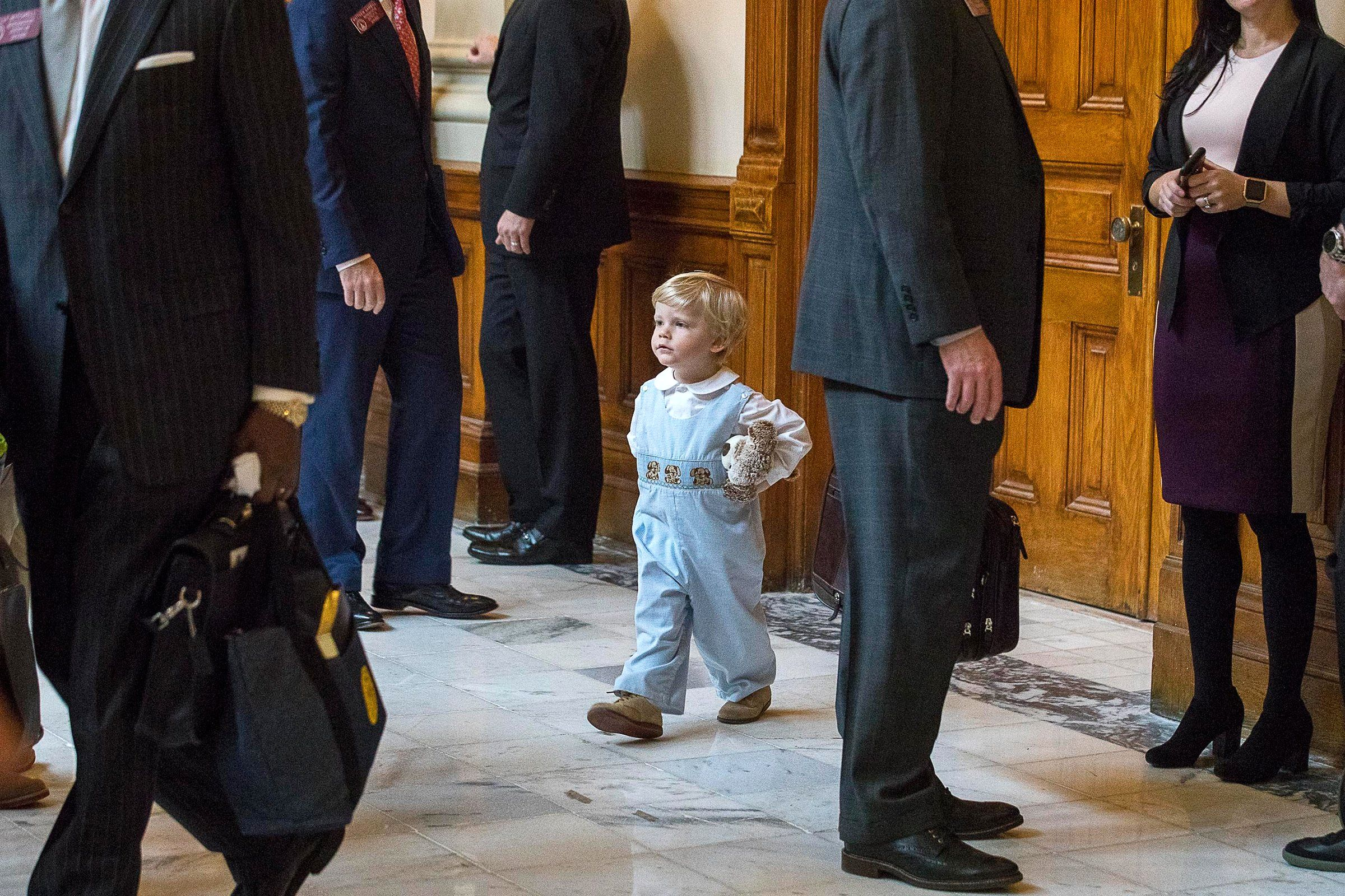 Two-year-old James Gambill of Cartersville navigates his way through Georgia lawmakers as he waits for his father, Rep. Matthew Gambill, a Republican, to be sworn in during the first session at the State Capitol building in Atlanta on Jan. 14.