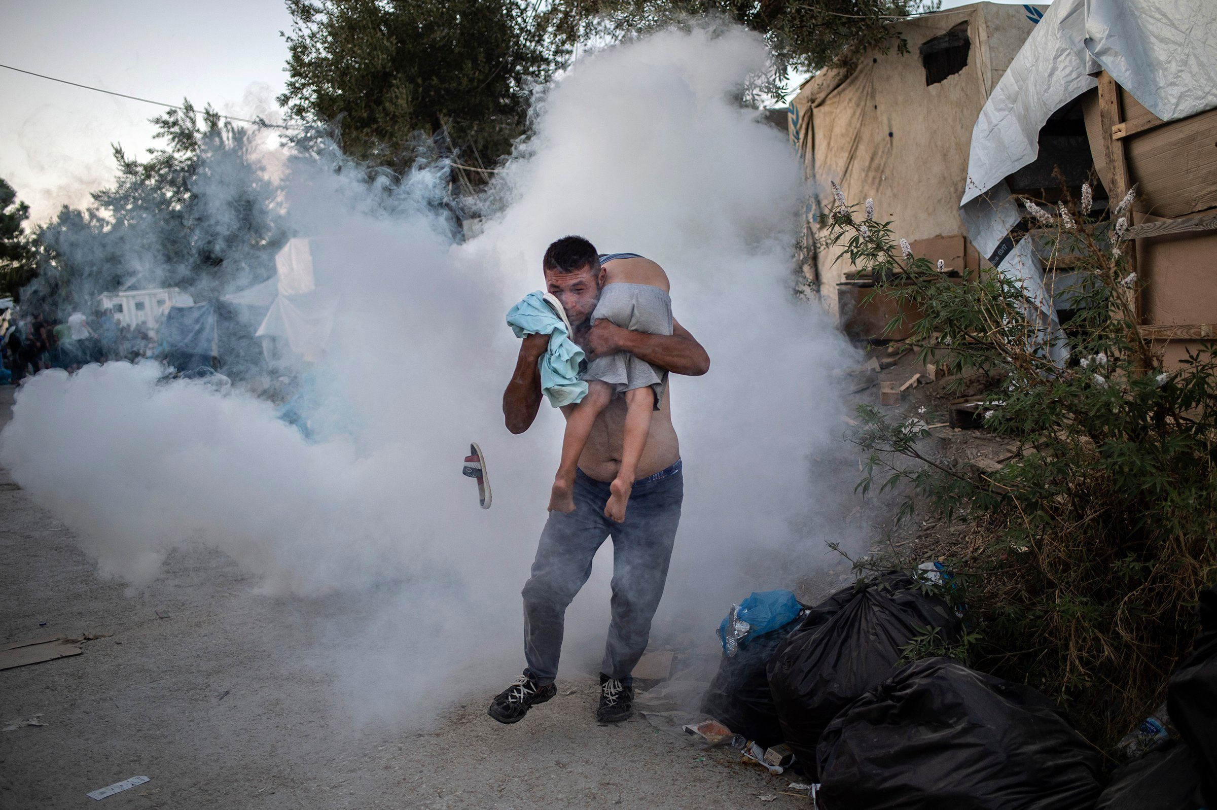 A man holds a boy during clashes with police outside the refugee camp of Moria on the Greek island of Lesbos on Sept. 29.