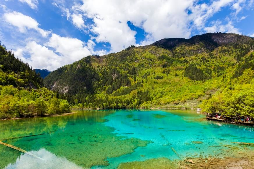 Slide 3 of 16: This lake in Jiuzhaigou National Park in southwest China sometimes acts like a mirror to reflect the surrounding landscape, which is particularly awe-inspiring in the fall. So it's no wonder that Five Flower Lake has a mythical history: A goddess is said to have dropped her mirror, which shattered into many pieces that formed the lakes of the park, including this one. The lake also provides a view right down to the fallen tree trunks at the bottom of its 16-foot depth, with varied, vibrant colors seeming to rise up from below. For the local people, this is a sacred lake; another legend says that wherever water from the lake is sprinkled, abundant flowers will grow. China also has one of the most beautiful beaches that naturally glow.