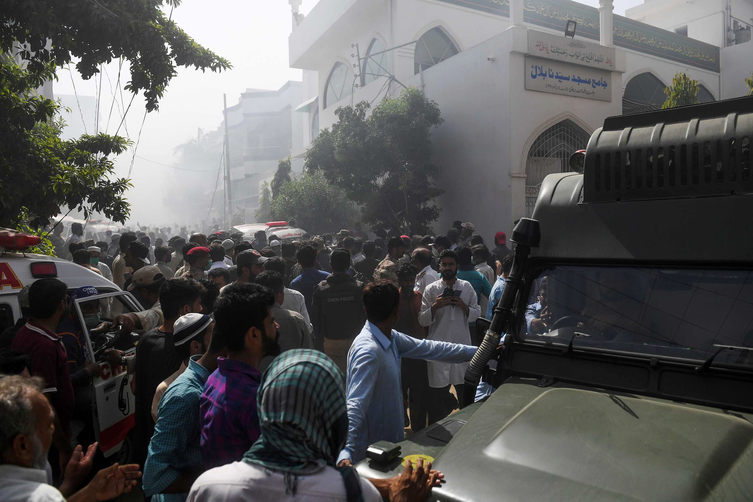 Rescue workers and onlookers gather near the site of the crash in a residential neighborhood in Karachi.