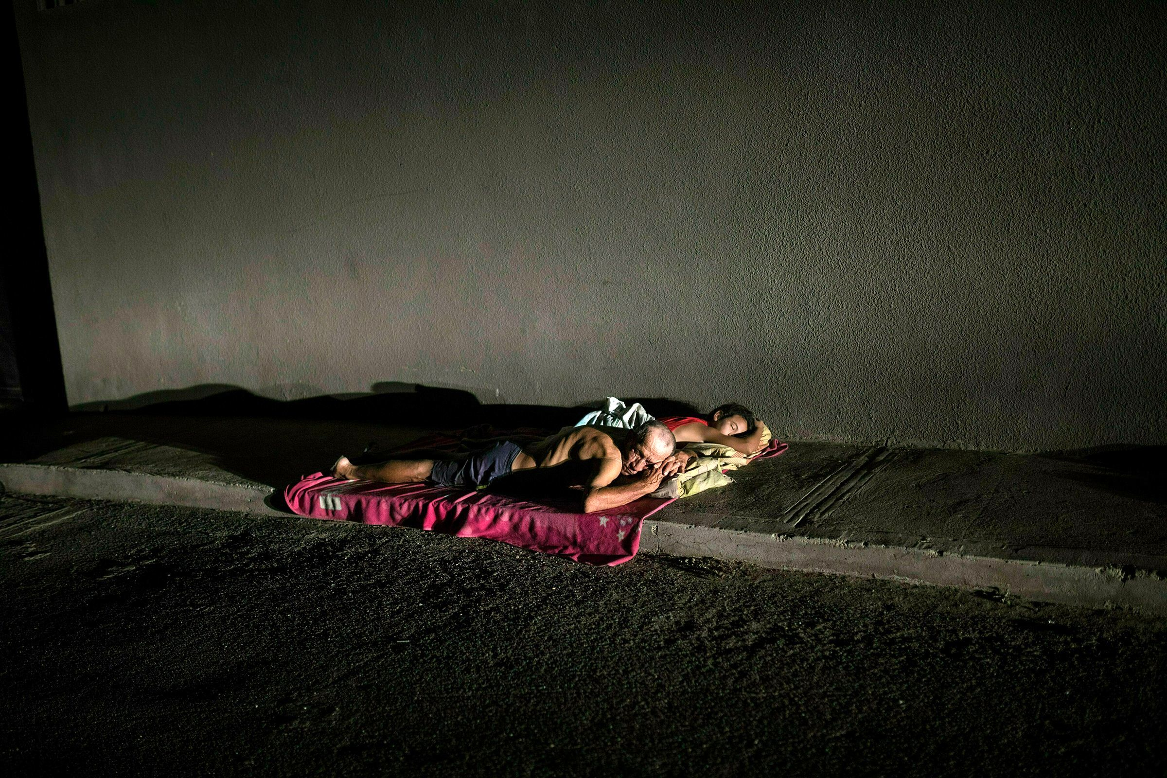 Due to a lack of electricity in their homes that prevents them from running air conditioners and fans, people sleep on the sidewalk to deal with the sweltering heat during a blackout in Maracaibo, Venezuela, on May 15.
