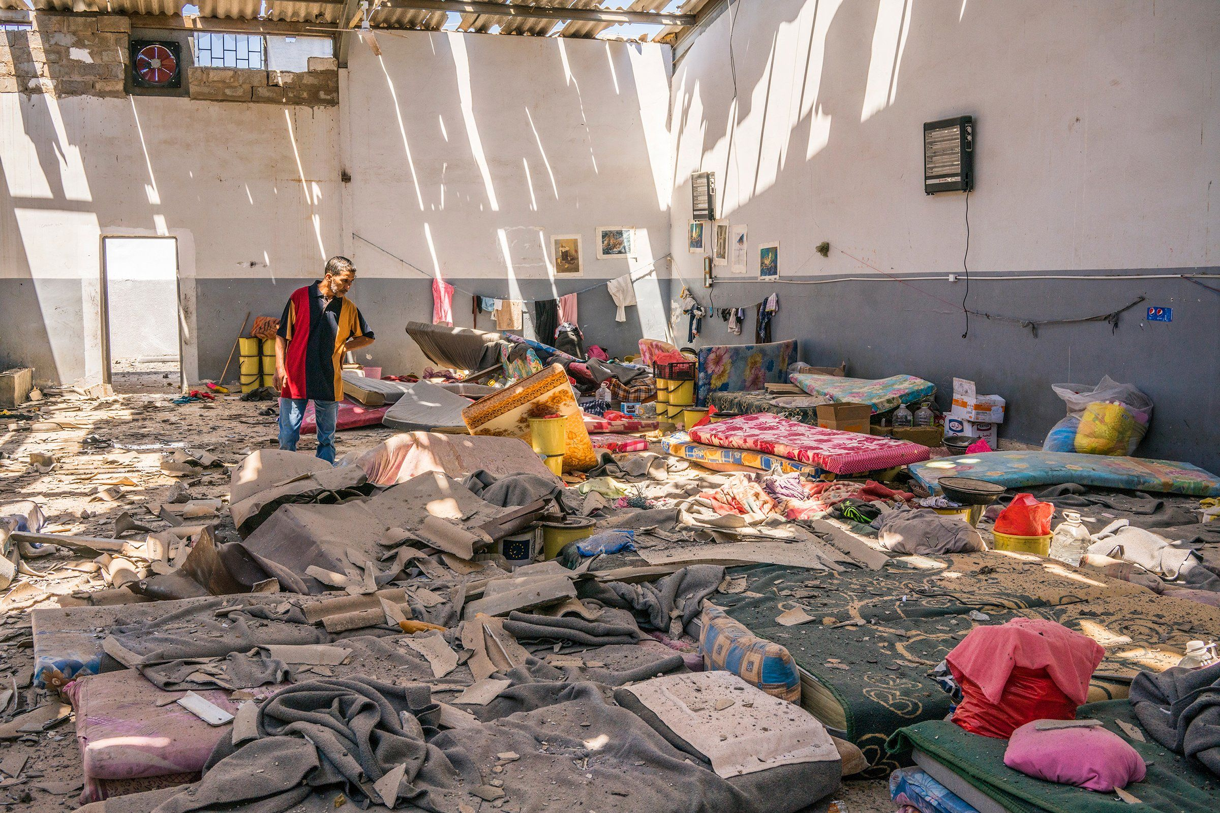 A man inspects damage to an area where migrants slept inside the Tajoura detention center near Tripoli, Libya, on July 3. An early morning airstrike there killed dozens.