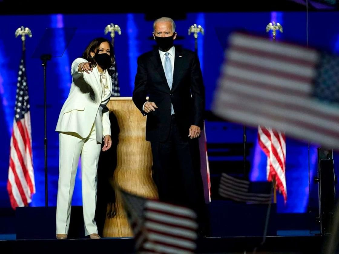 a person standing on a stage: President-elect Joe Biden and Vice President-elect Kamala Harris deliver remarks in Wilmington, Del., Nov. 7, 2020, after being declared the winners of the presidential election by the media.